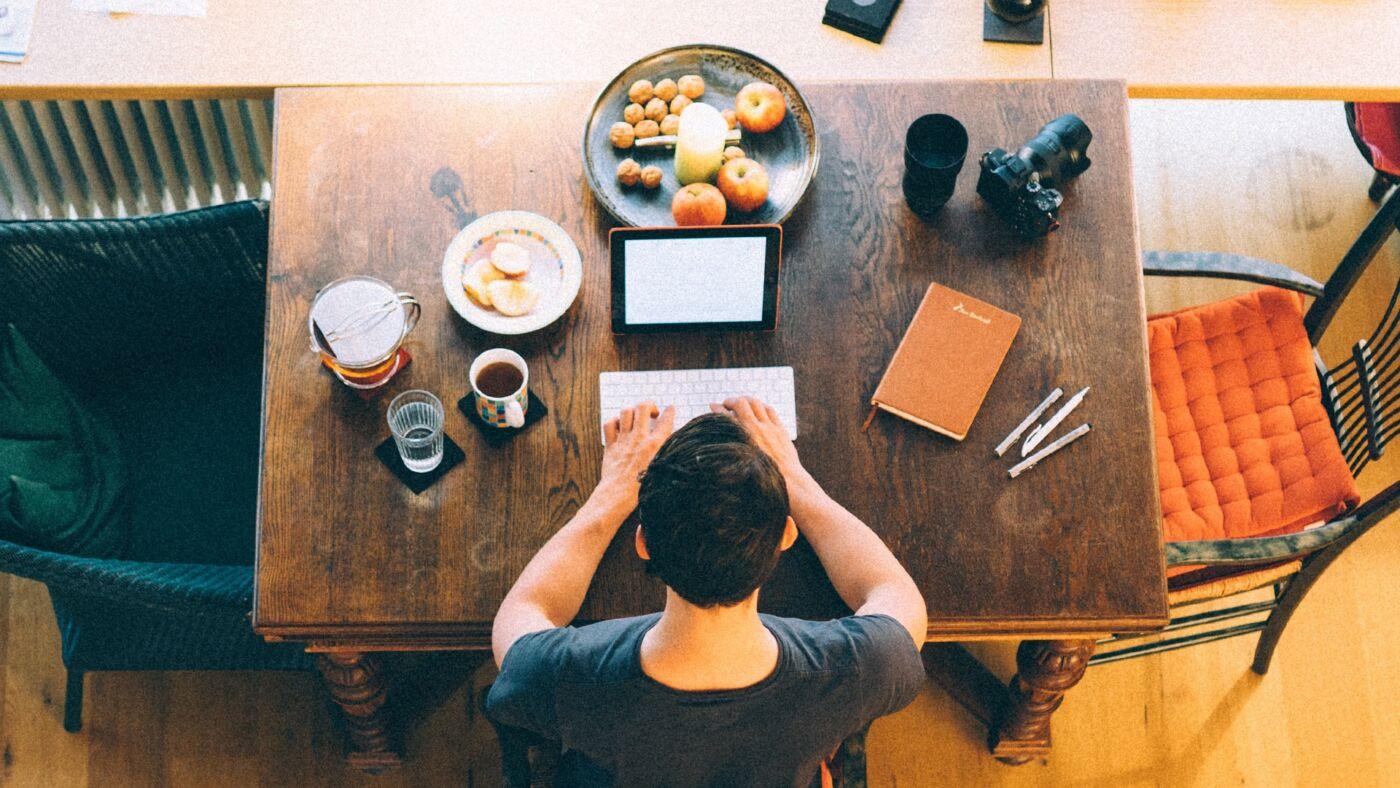 ragazzo lavora in smart working sul tavolo della cucina