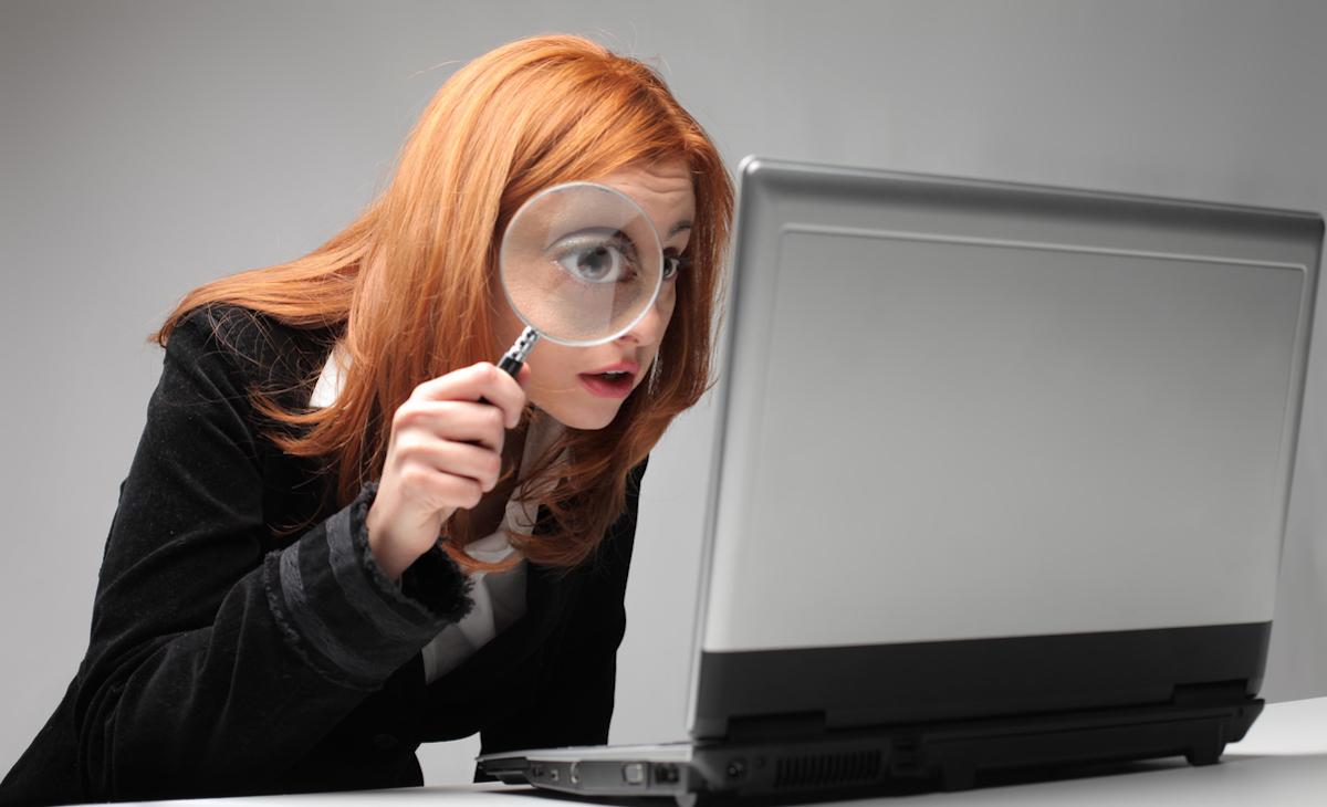 donna guarda con la lente d'ingrandimento il pc